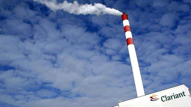 Aufnahme eines Clariant-Betriebsgebäudes mit einem rauchenden Kamin vor einem blauen, mit Schäfchenwolken überzogenen Himmel.