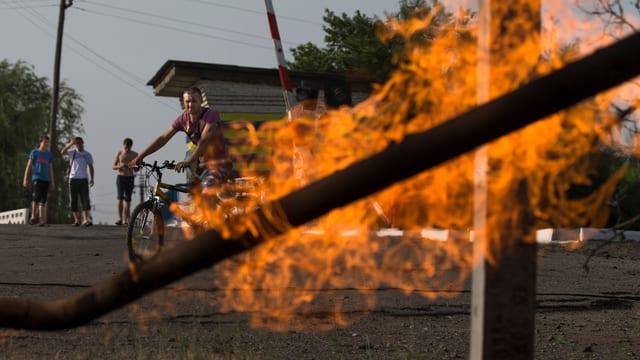 Brennendes Gasrohr im Vordergrund - dahinter ein Mann auf einem Fahrrad.