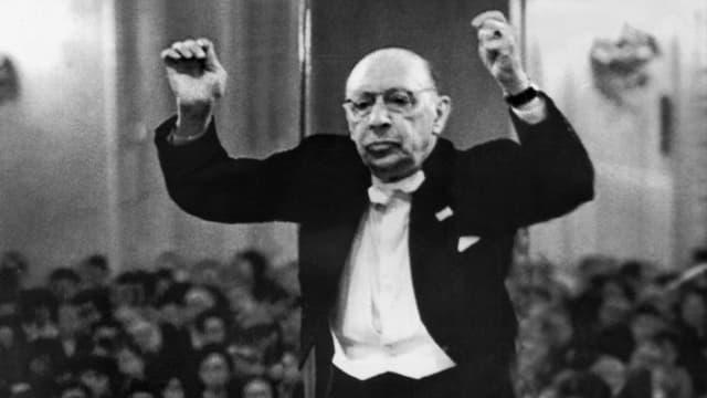Igor Strawinsky steht in schwarzem Anzug am Dirigentenpult und hält beide Hände in die Luft.