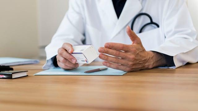 Ein Arzt mit Medikamentenschachtel in der Hand sitzt an einem Pult (anonymisiert)