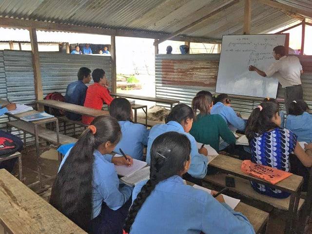 Blick in das Klassenzimmer. Der Lehrer schreibt auf eine weisse Tafel, die Kinder sitzen auf Holzbänken.