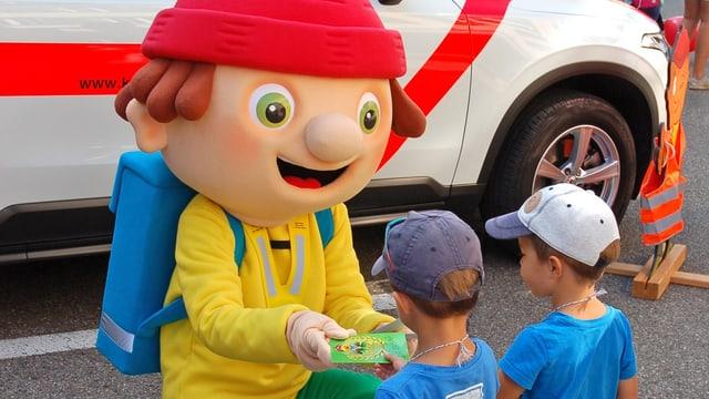 Maskottchen Simi Sicherli verteilt Malbüechli an kleine Kinder