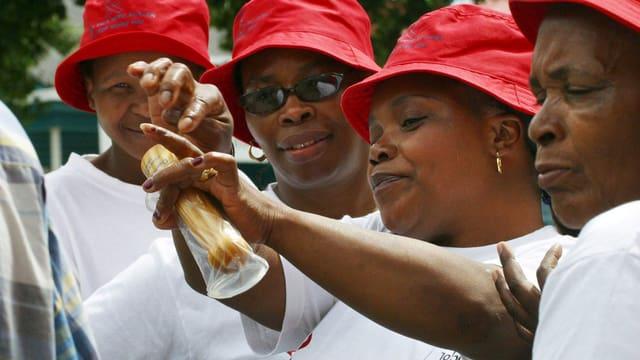 Vier Frauen führen den Gebrauch eines Kondoms an einem Vibrator vor.