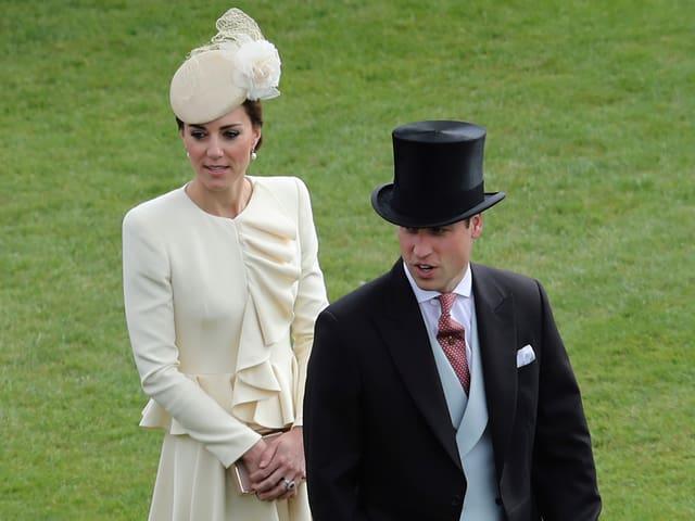 Kate und William auf einer Wiese stehend.