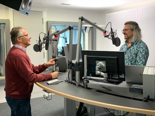 Zwei Männer vor Mikrofonen in einem Aufnahmestudio.