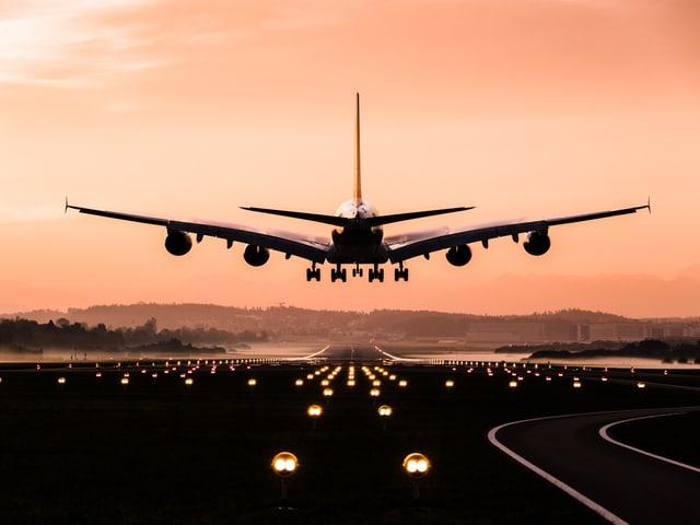 Ein Passegierflug setzt zur Landung am Flughafen Zürich an, der Morgenhimmel ist zart rosa gefärb.t