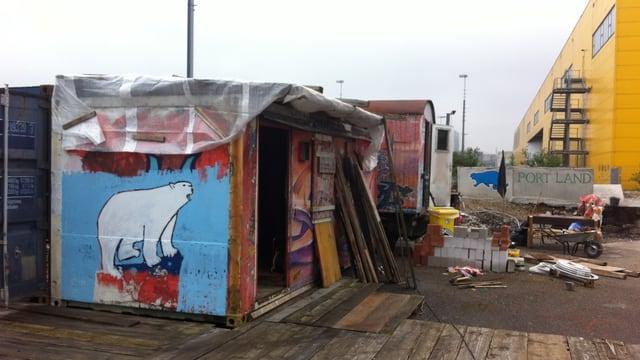 Eine Hütte auf einem Gelände, links vorne die Zeichnung eines Eisbären