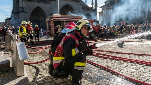 Ein Feuerwehrmann spritzt Wasser.
