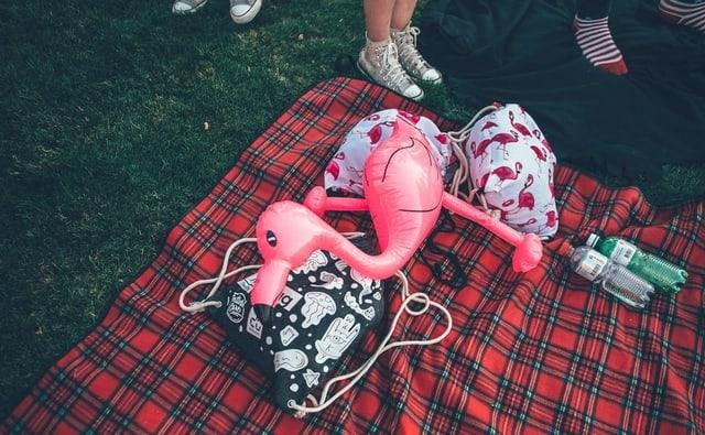 Aufblasbarer Flamingo und Rucksäcke liegen auf einem rot karierten Stofftuch