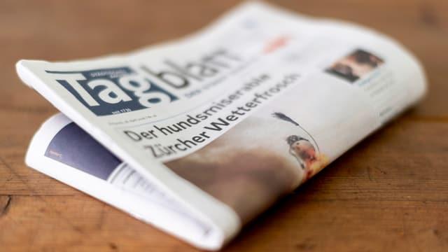 Eine gefaltete Zeitung liegt auf einem Holztisch