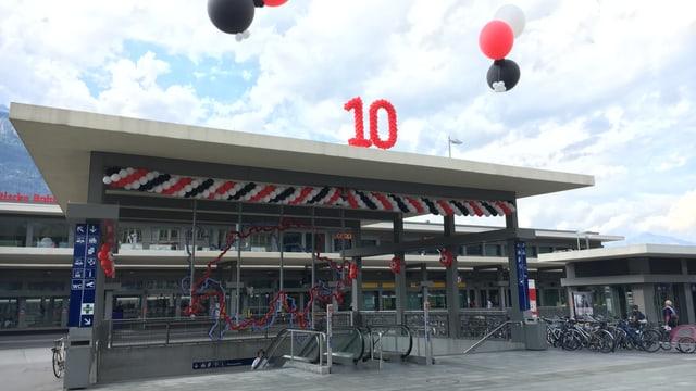 Il maletg mussa l'entrada da la staziun da Cuira decorada cun balluns.