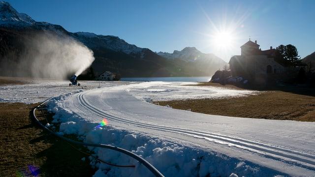 Eine Schneekanone auf einer Langlaufloipe aus Kunstschnee.