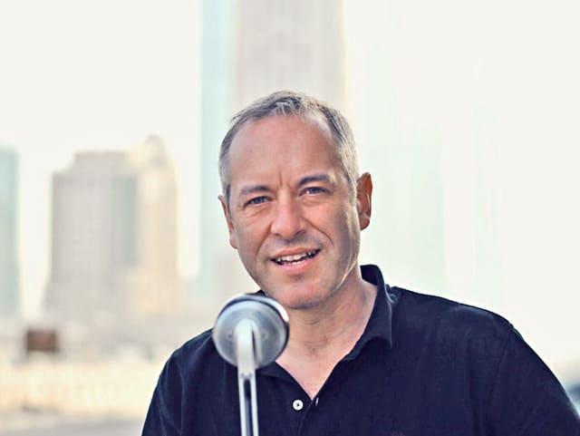 Korrespondent vor Wolkenkratzern, mit Mikrofon.