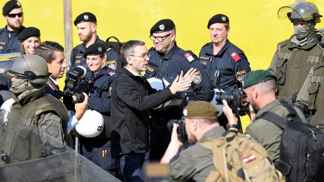 Mann in Anztug umringt von Soldaten und Polizisten.