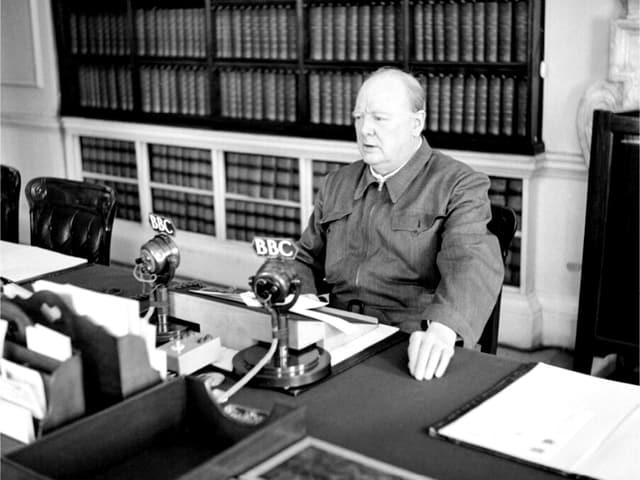 Mann sitzt am Schreibtisch – vor sich ein Mikrofon.