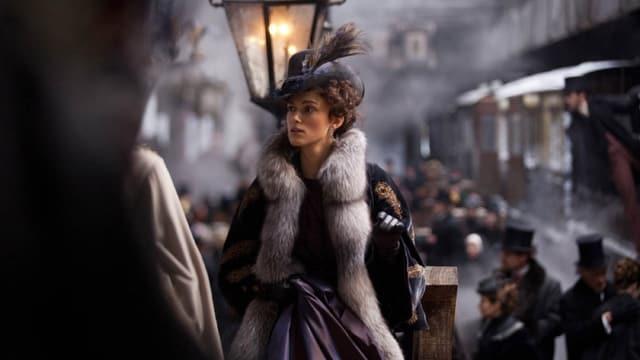 Anna Karenina, gespielt von Keira Knightely, steht am Gleis auf einem Bahnhof.