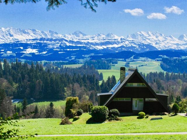 Haus, im Hintergrund die Alpen.