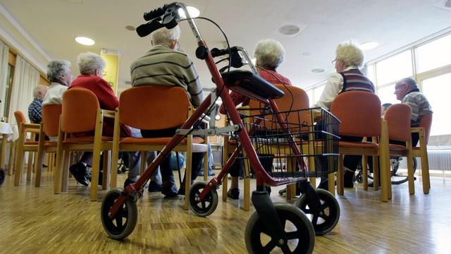 Eune Gruppe Senioren sitzt im Kreis, ein Rollator im Vordergrund.