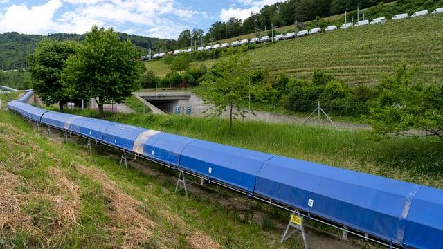 Förderband für Aushubmaterial, dahinter Autobahn und Bahngeleise mit Güterzug