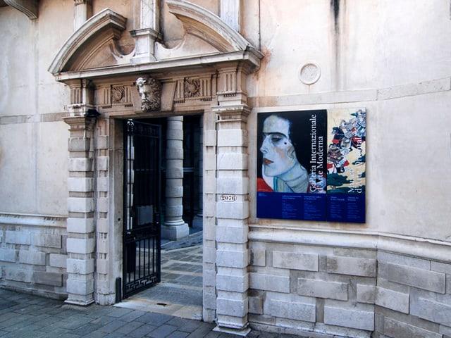 Eingang zu einem Museum in Venedig, neben der Tür weist ein Schild auf das Gemälde von Klimt hin.