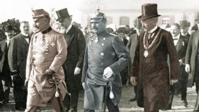 Drei Herren in Uniformen gehen auf einer menschengesäumten Strasse.
