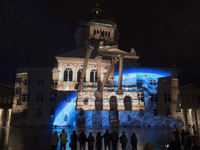 Projektion: Das Bundeshaus löst sich auf, seine Gebäudeteile fangen an zu schweben.