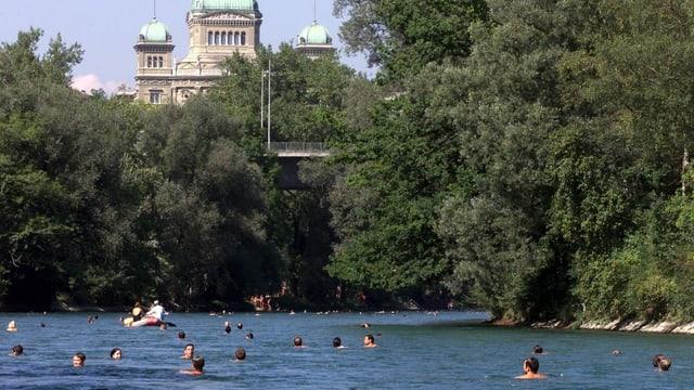 Bundeshaus und Aare, in welcher zahlreiche Badende schwimmen.