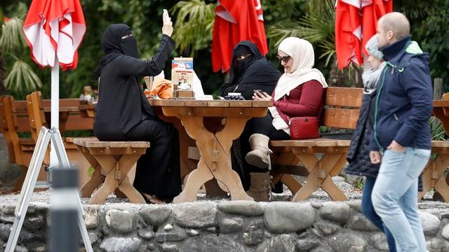 Dunnas muslimas sesan en in café ad Interlaken.