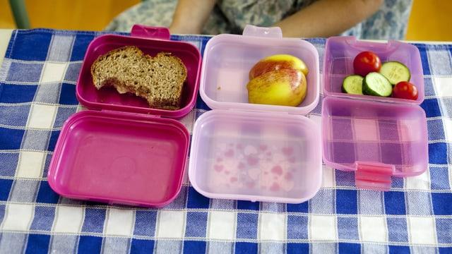 Drei geöffnete Znüni-Boxen mit Apfel, Gemüse und Brot.