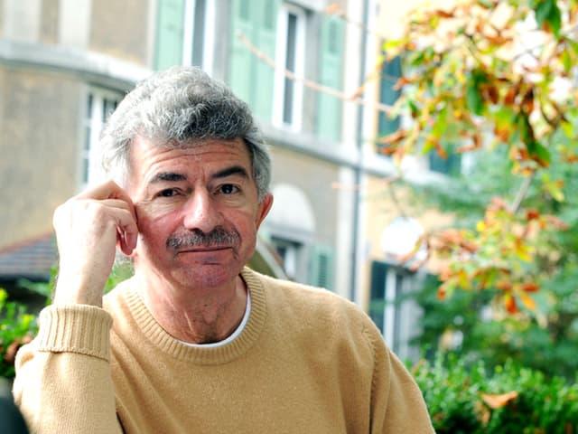 Das Proträt eines Mannes in hellgelbem Strickpullover, grauen Haaren und grauem Oberlippenbart.