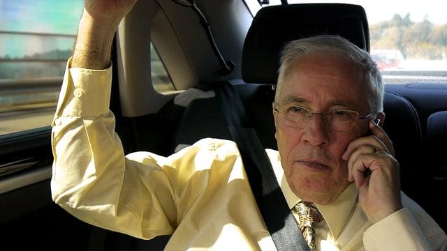 Christoph Blocher sitz auf dem Rücksitz eines Autos und telefoniert.