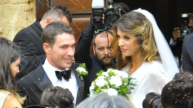 Elisabetta Canalis im Brautkleid und ihr Mann Brian Perri umgeben von Fotografen.