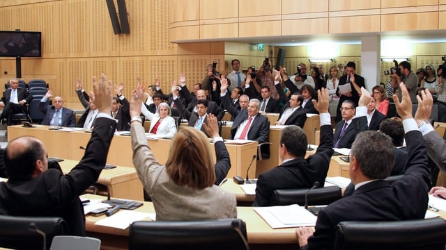Das zyprische Parlament stimmt ab; die Abgeordneten halten ihre Hände auf.