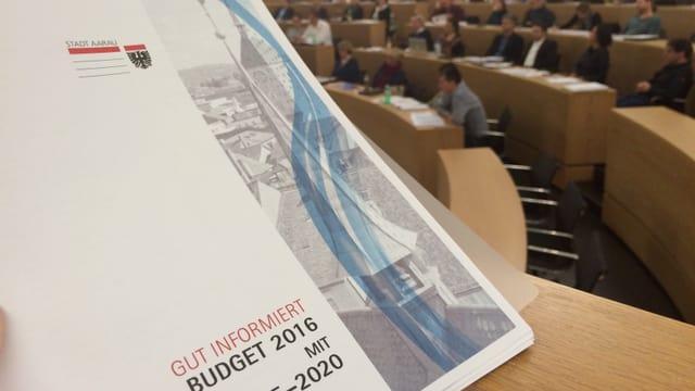 Einwohnerräte sitzen im Aargauer Grossratssaal, auf dem Pult steht die Budgetvorlage