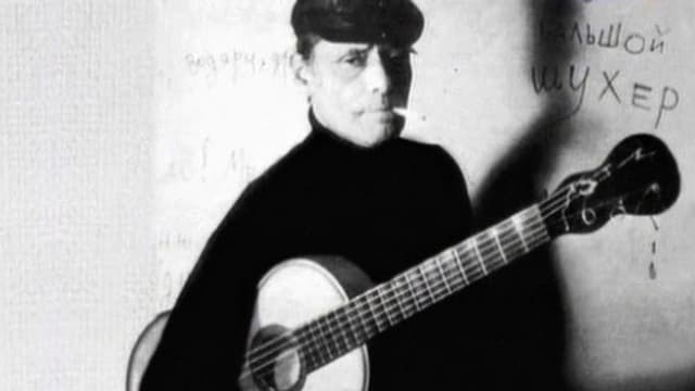 Schwarz-Weiss-Aufnahme von Aljoscha Dimitriewitsch, der mit der Gitarre unter dem Arm vor einer Wand steht.