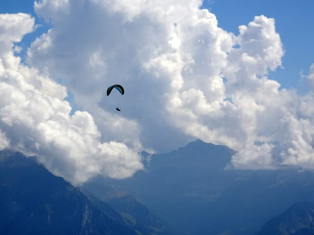 Quellwolken in den Bergen mit einem Gleitschirm im Vordergrund.