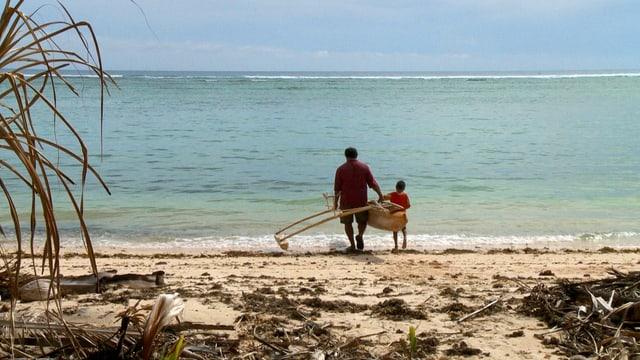 Ein Mann und ein Knabe gehen mit einem rudimentären Kanu ins Meer, Sicht von hinten.