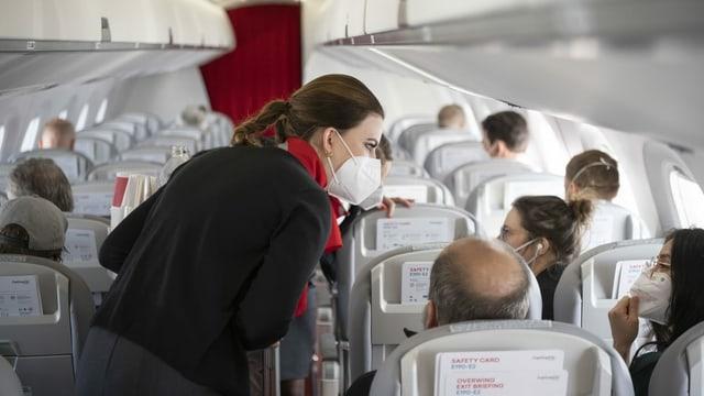 Passagiers e stewardess en in aviun.