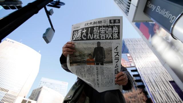 Eine Person hält zwischen Wolkenkratzern eine offensichtlich japanische Zeitung in der Hand, auf dem Titelbild ein Isis-Schlächter mit einer Geisel in orange neben sich kniend.