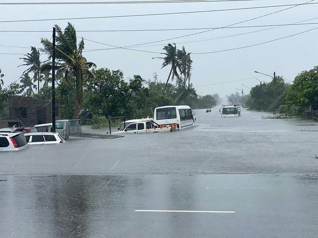 Autos treiben im überschwemmten Fluss.