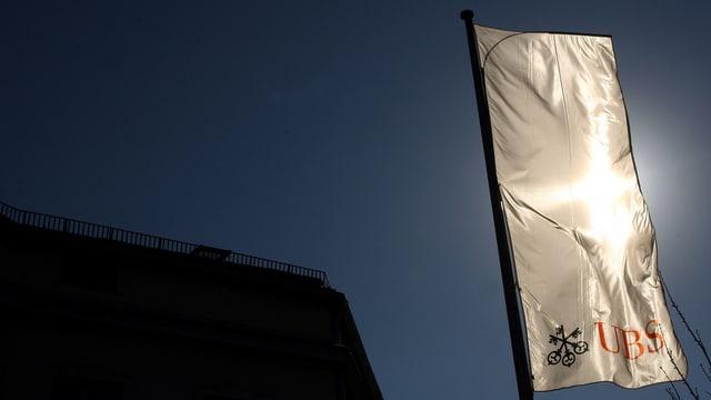 Eine Fahne der UBS weht vor der Sonne (keystone/archiv)