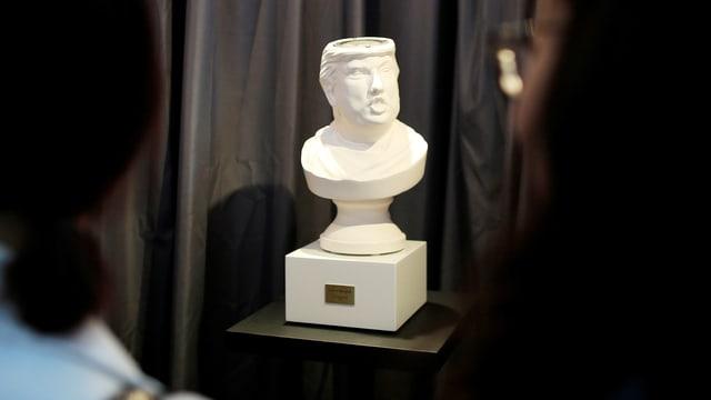 Besucher einer Tech-Messe betrachten ein Gadget in Form einer Trump-Büste mit offenem Kopf.