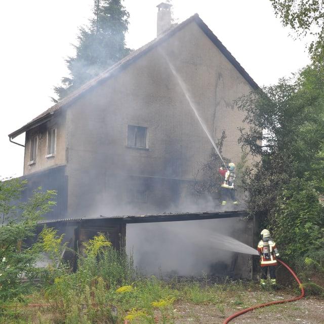 Zwei Feuerwehrleute spritzen Wasser an eine Hausfassade