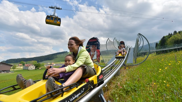 Eine Frau fährt mit ihrem Kind auf der Bobbahn.
