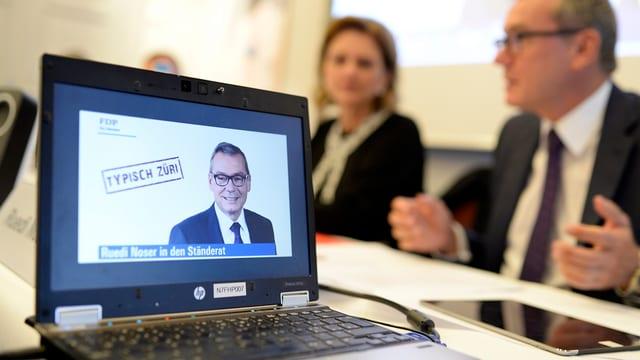 Laptop-Bildschirm mit Wahlplakat daruf, dahinter unscharf Menschen