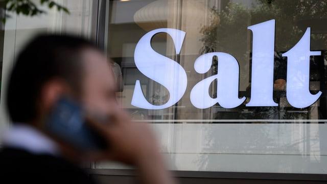 Ein Mann telefoniert vor einem Salt-Laden