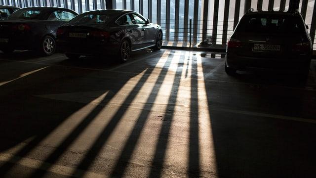 Parklücke in einem Parkhaus, durch dessen halbtransparente Wand Sonnenstrahlen in einem Gittermuster auf den Boden fallen.