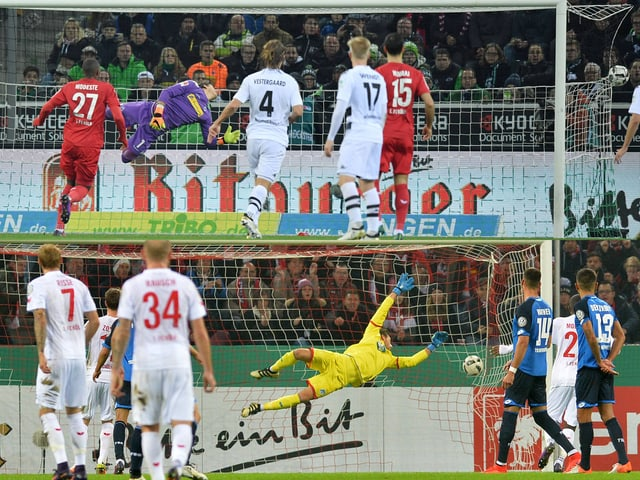 Marcel Risse vom 1. FC Köln schiesst ein Tor gegen Gladbachs Yann Sommer.