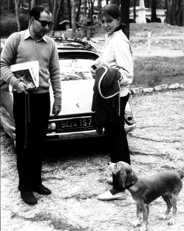 Jean Luc Godard und seine damalige Frau Anne Wiazemsky stehen vor einem Auto und schauen einen Hund an.