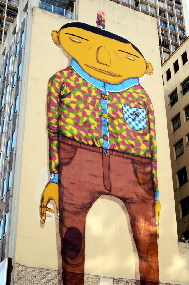 Wandbild: Ein Mann mit grossem, breitem Kopf, langezogenen Augenbrauen, Hemd und Hose.